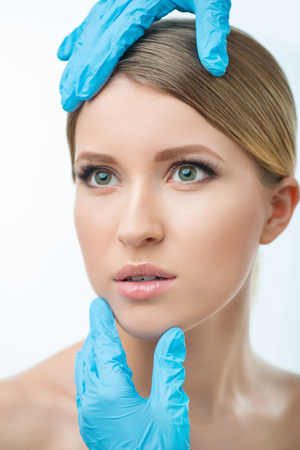 plastic glove: Getting ready for operation. Portrait of young pretty woman looking aside while plastic surgeon examining her Stock Photo