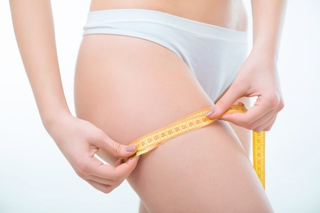 half nude: Keep on diet. Close up of hip of slim woman holding measuring type and measuring it while standing isolated on white background Stock Photo