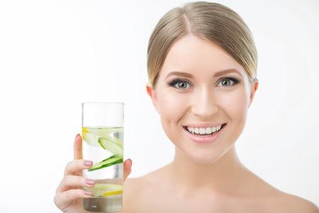 ombligo: Mantenerse sano. Mujer agradable alegre que sostiene un vaso de agua y beberlo mientras que de pie aislado en fondo blanco Foto de archivo
