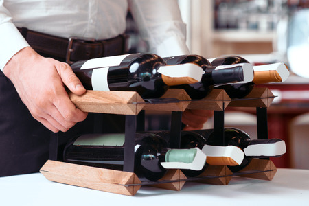sommelier: Only best wine. Close up of wine holder in hands of professional sommelier holding it and putting on the surface of table while doing his job