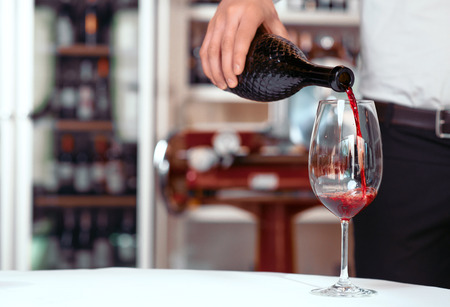 sommelier: Only best one. Close up of bottle of wine in hands of sommelier holding it and pouring it into the chalice while being involved in work Stock Photo