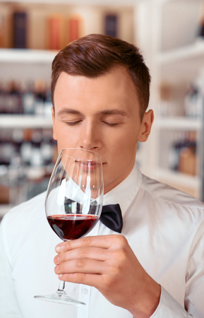 sommelier: Gorgeous aroma. Portrait of pleasant professional sommelier holding wine glass and tasting it while closing his eyes Stock Photo
