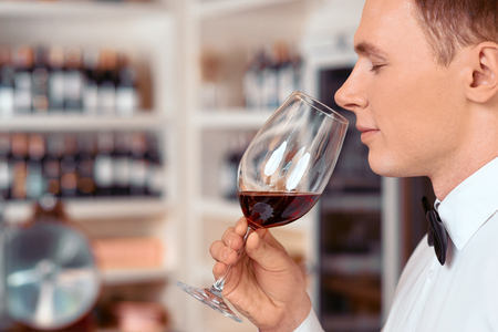 sommelier: What a nice aroma. Pleasant professional sommelier holding wine glass  and tasting it while closing his eyes Stock Photo