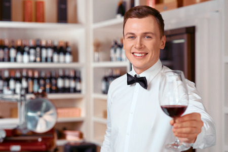 sommelier: Full of positivity. Handsome vivacious smiling   sommelier holding wine glass and going to taste it while being involved in work Stock Photo