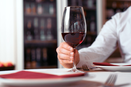 enjoyable: Enjoyable time. Close up of wineglass in hands of a man sitting at the table in the restaurant