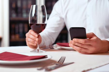 hands connected: Always connected. Close up of mobile phone in hands of modern man and holding glass of wine while resting in the restaurant