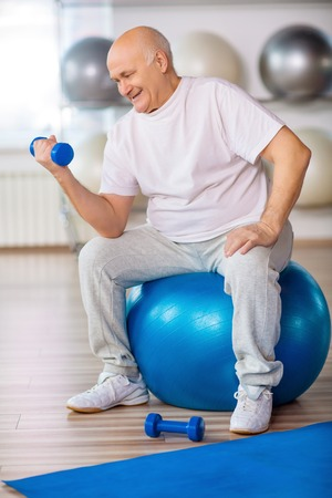 rubber ball: Want to be health. Pleasant senior man sitting on the rubber ball and keeping weight in hand while doing exercise Stock Photo