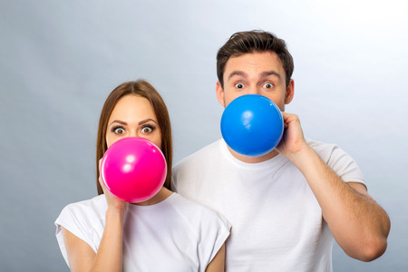 brighten: Brighten your life. Cheerful pleasant young couple blowing balloons and having fun while standing isolated on grey background