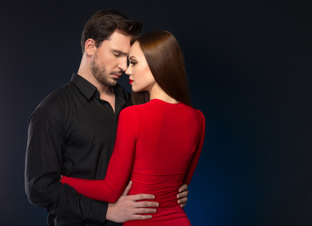 sexually: Moment of passion. Sexually attractive woman standing with her handsome boyfriend on black background and expressing flame of love