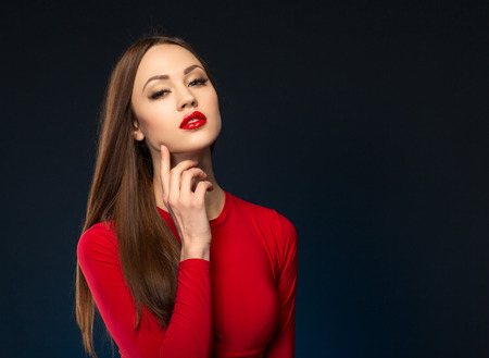 lustful: Magnetic glance. Sexually attractive beautiful woman holding her finger on the chick and looking at you while seducing Stock Photo