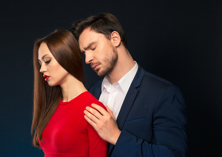 In whirlwind of passion. Handsome pleasant man closing his eyes and embracing attractive woman while standing isolated on black background