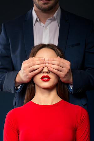 guess: Guess who.  Mysterious man closing eyes of attractive woman while standing isolated on black background