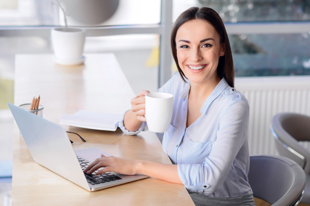 Have some rest. Cheerful content business woman working on the laptop and drinking tea while smiling at work Stock Photo