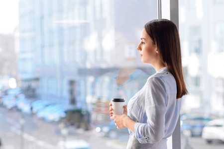 Seul dans la vie active. Belle sombre café femme potable et debout près de la fenêtre tout en pensant