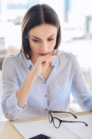 corporal: Something went wrong. Disappointed young woman sitting at the table and being involved in work while feeling sad Stock Photo