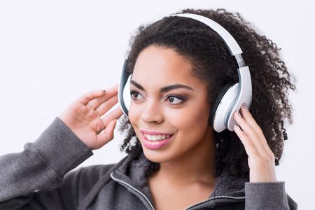 mulatto woman: Feel the beat. Cheerful nice mulatto woman wearing headphones and listening to music while looking aside