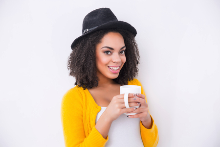 mulatto: Enjoy your life. Delighted beautiful mulatto woman holding cup and drinking tea while smiling