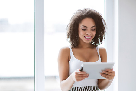 mulatto woman: Modern way of life. Content positive mulatto woman smiling and holding tablet while standing near window Stock Photo