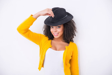 to be pleasant: Be fashionable. Cheerful pleasant mulatto woman holding hat and wearing it while smiling
