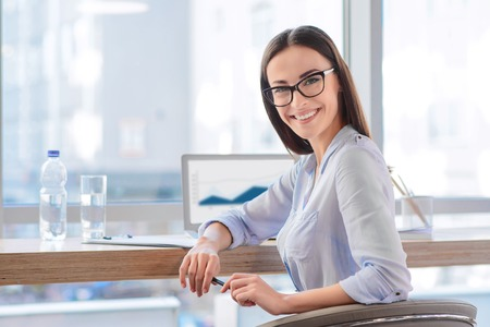 harming: Have a nice day. Cheerful smiling businesswoman sitting at the table and holding pen while working Stock Photo
