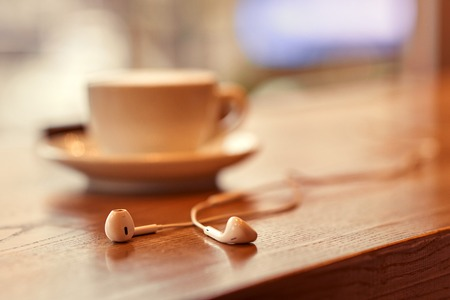 peacefulness: Enjoy peacefulness. Selective focus of headphones lying on the surface of table near cup with coffee