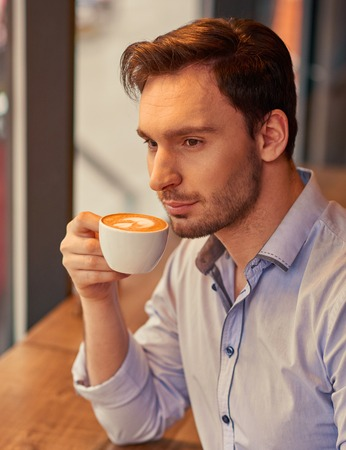 revel: Revel in taste. Pleasant content handsome man sitting at the table and drinking coffee while  resting in the cafe