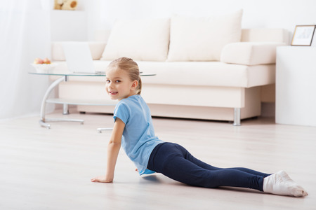 Gesundheitswesen Aktivität. Kleines nettes Mädchen tut Übungen während allein zu Hause zu bleiben