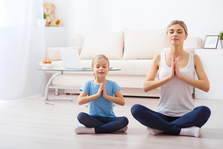 Take a deep breath. Beautiful mother and her lovely daughter are feeling relaxed while doing yoga together 免版税图像