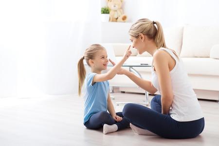 Abbindezeit. Junge schöne Mutter ist zu Hause mit ihrem netten lächelnden Kind spielt