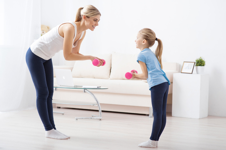 keeping fit: Keeping fit together. Young mother is doing exercised with her lovely daughter with kettlebells  while being at home Stock Photo