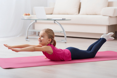 Little fan of yoga. Adorable little girl is smiling while enjoying doing exercises at home alone