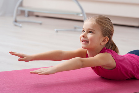 mat like: Keeping healthy lifestyle. Close ou of cute little girl is lying and stretching while working out at yoga mat
