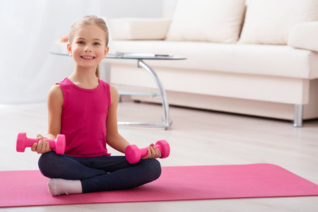 buena postura: postura correcta es importante. Adorable niña bonita está sentado y sonriendo mientras sostiene pesas