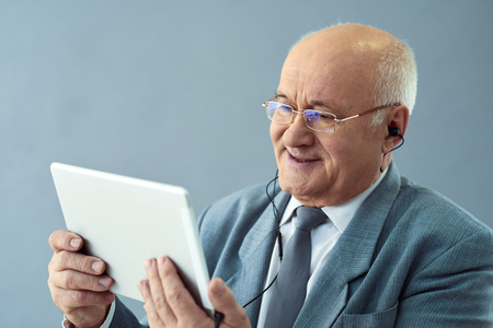interested: Internet technologies in business. Close up shot of old smart man with earphones holding tablet and looking interested.
