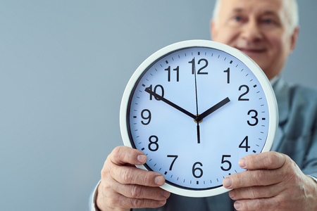 showed: Manage your time. Close up shot of clock showed by smiling man isolated on grey background.