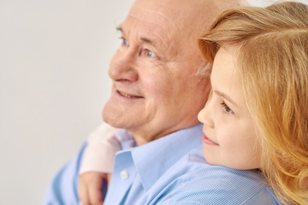 Loking in one direction. Portrait of  pretty small girl lookting somewhere with her loving grandfather  hugging him, isolated on white background