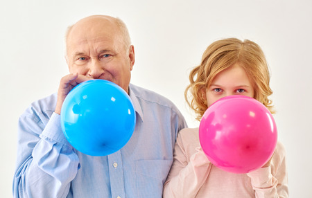 powerfully: Together more cheerful. Grandfather and granddaughter inflating pink and blue balls in studio on white background.