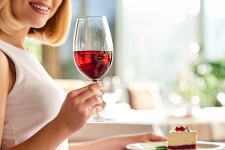 important event: Important event. Close up shot of glass in hand of young nice woman in the restaurant. Stock Photo
