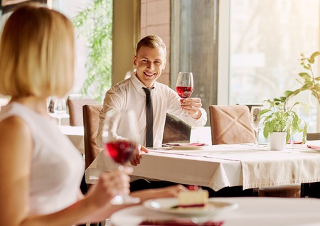 strangers: Unexpected meeting. Handsome young man is looking at beautiful woman while sitting separately in the restaurant.