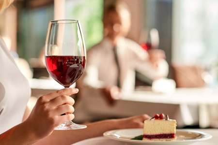 Relaxing time. Close up shot of wine glass hold by woman having dessert at the restaurant.