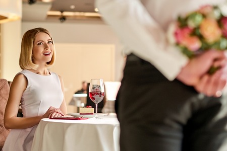 delightful: Delightful evening. Young beautiful woman is looking impressed by man with flowers in the restaurant. Stock Photo