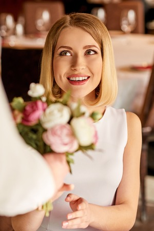 romantics: Making a surprise. Shot of young stunning woman getting flowers from nice man in the restaurant. Stock Photo