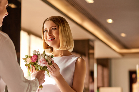 appreciating: Appreciating his attention. Young beautiful woman is taking flowers from man and smiling happily. Stock Photo