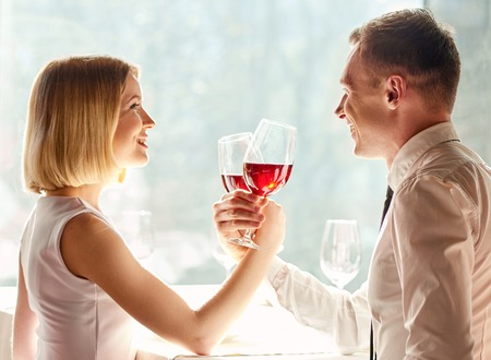 romantics: Celebrating their love. Shot of smiling couple holding glassed of wine and happily looking at each other.