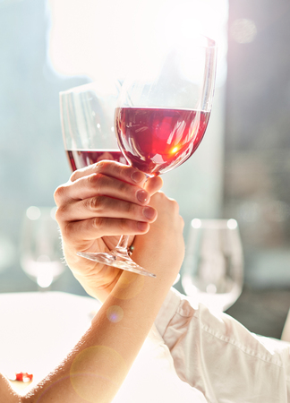 cropped shot: Successful date. Cropped shot of two persons hands holding glasses of wine at the restaurant.