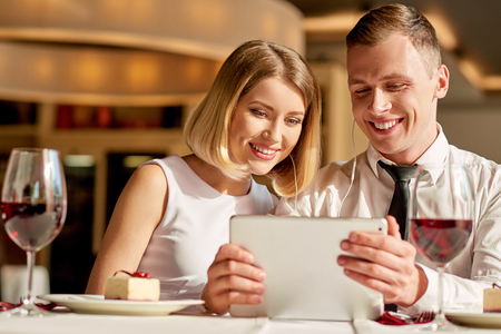 online world: Discovering online world. Shot of lovely young couple staring at tablet and smiling while sitting at the restaurant.