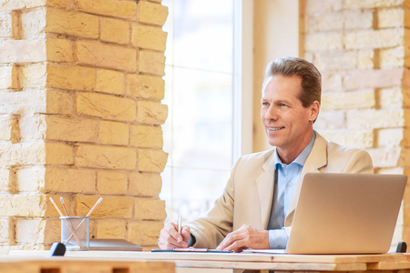 upbeat: Follow your tasks. Positive pleasant upbeat man making notes and looking aside while working at the table