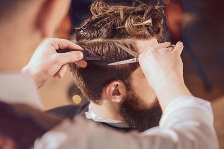 Essere precisi. Piacevole uomo barbuto seduto dal barbiere, mentre barbiere professionista facendo di lui un taglio di capelli con le forbici.