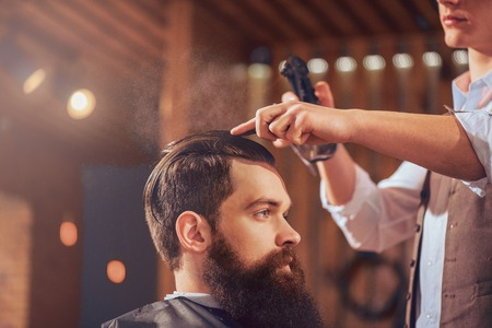 hairspray: Creativity is switched on. Handsome bearded man sitting in the barbershop while professional barber holding hairspray while styling his hair