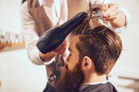 Make it dry. Bearded handsome man sitting in the barbershop while skillful barber drying his hair with hairdryer Stock Photo